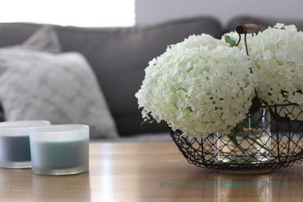 Lovely white hydrangeas in a wire basket on top of a coffee table upcycled with Annie Sloan Chalki Paint in old white. www.chalkingupsuccess.com