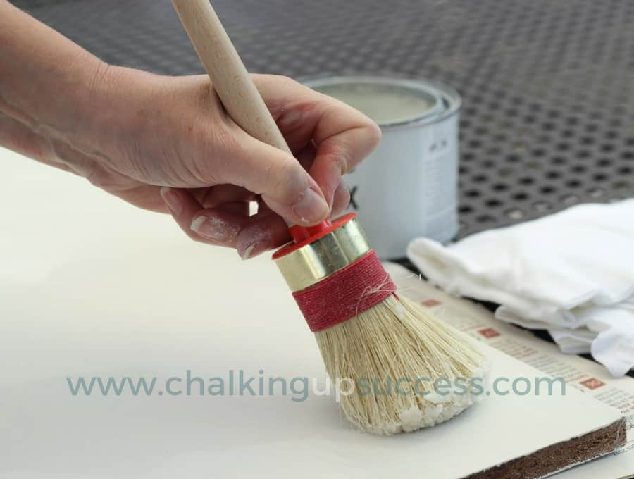 Applying Annie Sloan white wax to one of the shelves using a round brush