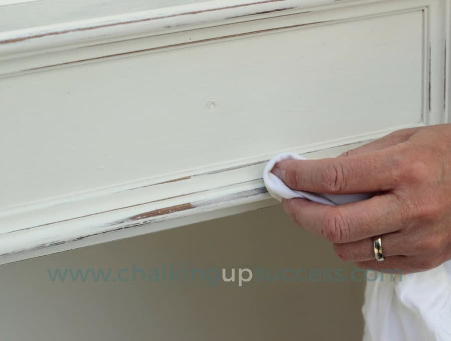 Applying white way to the edges of the bookcase drawers after distressing