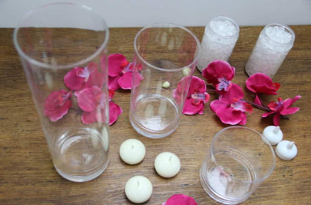 Tall glass jars, pink orchids and floating candles. From the post How to create a stunning valentine's day tablescape www.chalkingupsuccess.com
