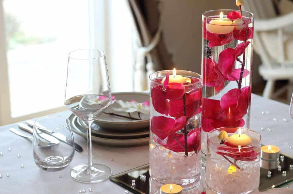 Stunning table setting for two. Tall glass vases filled with beautiful pink orchids, water and floating candles. From the post How to create a stunning valentine's day tablescape www.chalkingupsuccess.com
