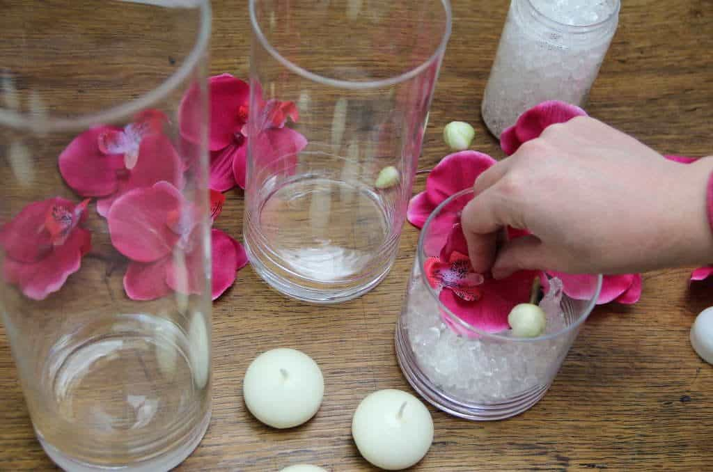 Adding the pink coloured orchid to the glass jars. From the post How to create a stunning valentine's day tablescape www.chalkingupsuccess.com
