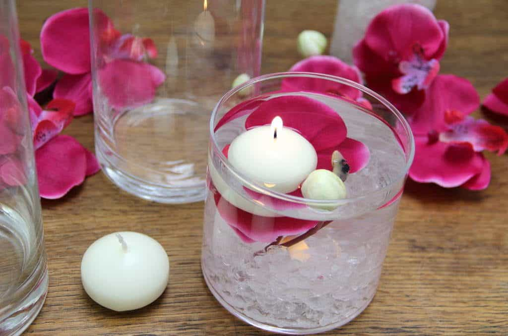 ImGlass vase with beautiful pink orchid flower and a white floating candle. From the post How to create a stunning valentine's day tablescape www.chalkingupsuccess.com