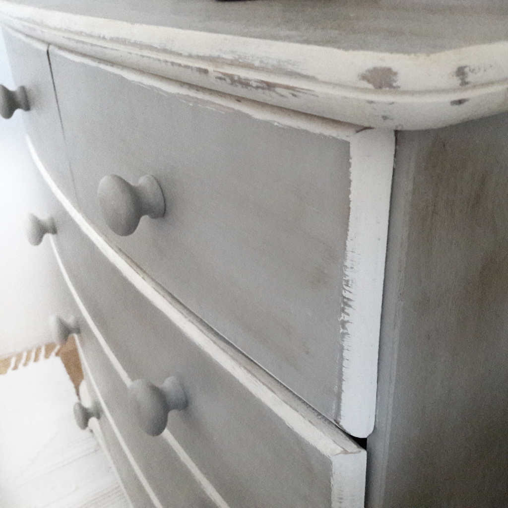 Bedroom chest of drawers painted with Annie Sloan chalk paint in Paris Grey. The edges of the drawers are painted white and distressed.