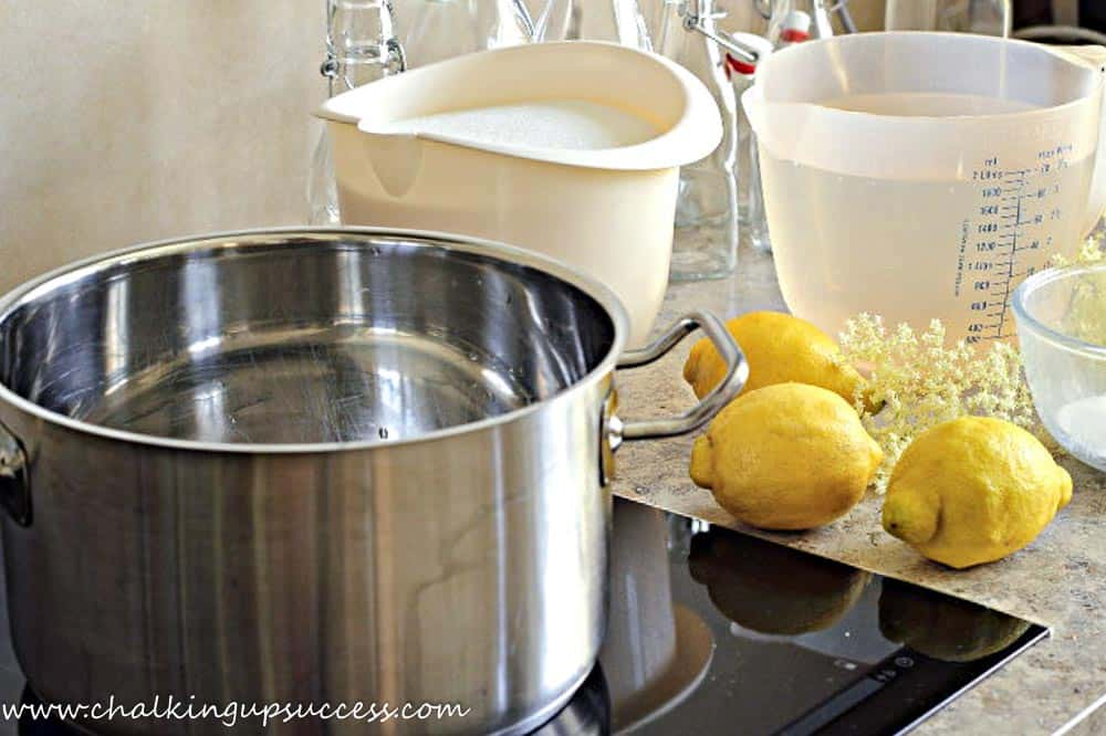 A saucepan of water and the ingridients to make Elderflower Syrup. Lemons, sugar and water