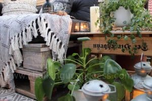 The beer crate side table fits perfectly in the space to the side of the pallet sofa. On the table are some lanterns a white church candle and a green trailing plant. A pilea plant and some metal lanterns stand on the floor in front of the table. #palletsofa #outdoorliving #diysidetable #palletsectional #boho #palletsofadiy #palletsofaoutdoor #recycledpallets