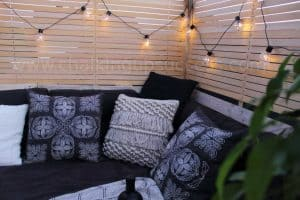 Black and cream cushions on the DIY pallet sofa - above you can see my DIY privacy screen draped with festoon party lights for outdoors #palletsofa #outdoorliving #diysidetable #palletsectional #boho #palletsofadiy #palletsofaoutdoor #recycledpallets
