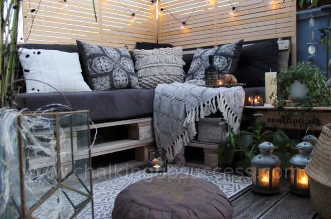 A stunning black boho-chic outdoor seating area with a pallet sofa stained white and a beer crate side table. Accessories include, black & cream embroidered cushions and chequered throw, and lots of glass lanterns with flickering candlelight. Festoon lights are draped across a DIY privacy screen made from recycled wooden blind slats. A chic outdoor rug and lots of lovely plants complete the look. All the details are on the blog. #palletsofa #outdoorliving #diysidetable #palletsectional #boho #palletsofadiy #palletsofaoutdoor #recycledpallets #indooroutdoorrugs