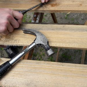 Showing how to remove staples from a pallet with a hammer and a chisel #palletsofa #outdoorliving #diysidetable #palletsectional #boho #palletsofadiy #palletsofaoutdoor #recycledpallets #indooroutdoorrugs