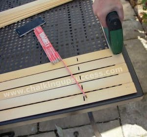 How to make a privacy screen from recycled blinds. Really easy DIY - create a privacy screen for your garden with recycled blinds or use it as a backdrop for photos or for your office. chalkingupsuccess.com photo shows a stapler being used to staple the slats to the frame #boho #outdoorliving #palletsofa #diy #privacyscreen #sunshade #sunscreen #recycledblinds #recycledvenetianblinds #outdoorspace #palletfurniture #beercratetable