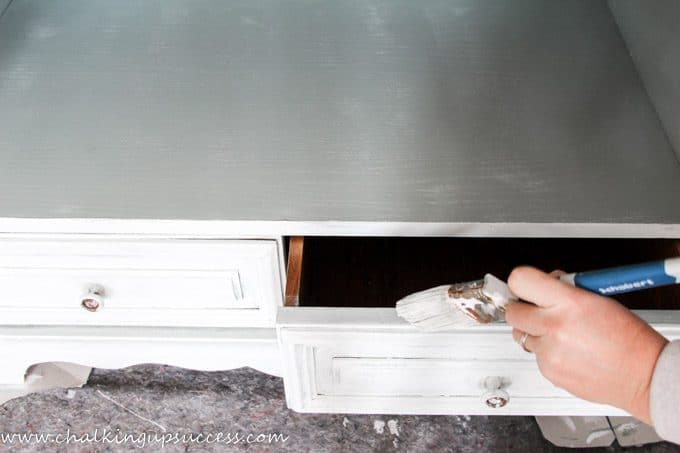 Gently painting the top of the drawers of the media stand with a chalk paint wash in white