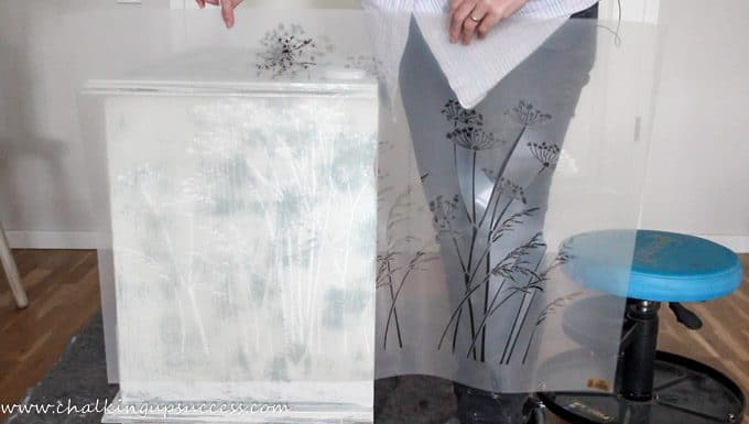 Picture shows a person holding up a large stencil depicting cow parsley and grasses. Next to the person is a chalk painted media stand which has been painted in Annie Sloan Chalk Paint in Duck Egg Blue with a wash of 'Old White' over the top.