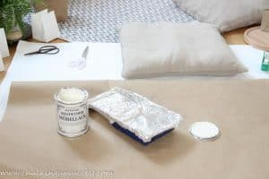 A can of white chalk paint and a painting tray lined with aluminium foil rest on a square of brown packing paper.