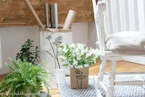 photo shows a DIY giant paper bag painted white with the top rolled down to reveal the natural tan colour of the inside. The bad is stencilled with dandelion seedheads in the colour 'Graphite'. A smaller bag in natural brown holds a vase of white freisers.