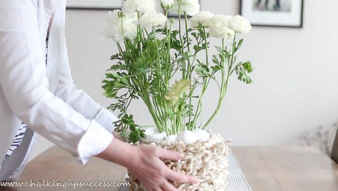 A person placing a basking of Persian Buttercups onto a table. From the blog post 'A simple Easter tablescape by 'Chalking Up Success'