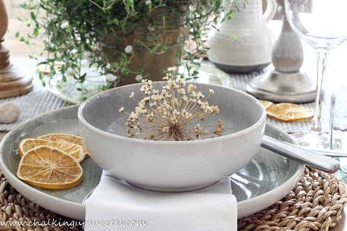 A simple Summer tablescape - grey/green stoneware bowl and plate - dried orange slices are arranged around the side of he plate and an Alium seedhead is placed inside the bowl.
