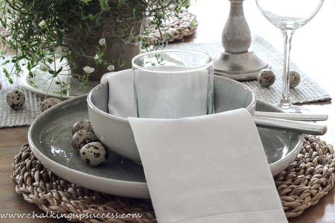 Grey/green stoneware plate and bowl as part of a simple Easter tablescape. A napkin is a white napking and on top of that a green tinted water glass. From the blog, Chalking Up Success.