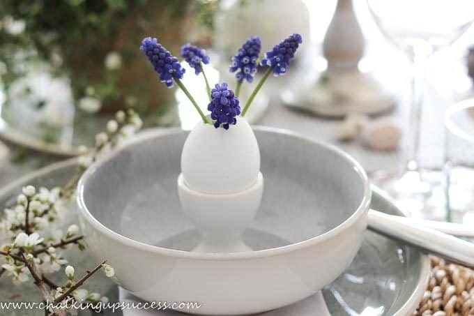 A white eggcup stands inside a grey/green stoneware bowl. The eggcup is filled with a hollow white eggshell which is being used as a vase to hold five pretty purple hyacinth flowers - from the blog, Chalking up success.