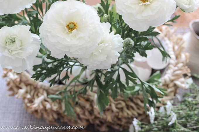A basket filled with white flowers and the earth hidden by white eggshells.