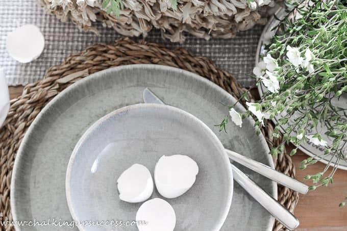 Grey/Green rustic plate and bowl as part of a simple Easter tablescape. Three white eggshells rest inside the bowl.