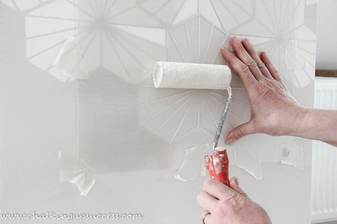A person rolling paint onto a wall stencil.