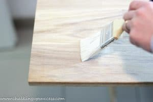 using a paint brush to apply the oil/wax mix to the oak shelving boards.