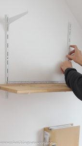 sliding the middle bracket behind the shelf to measure the correct distance