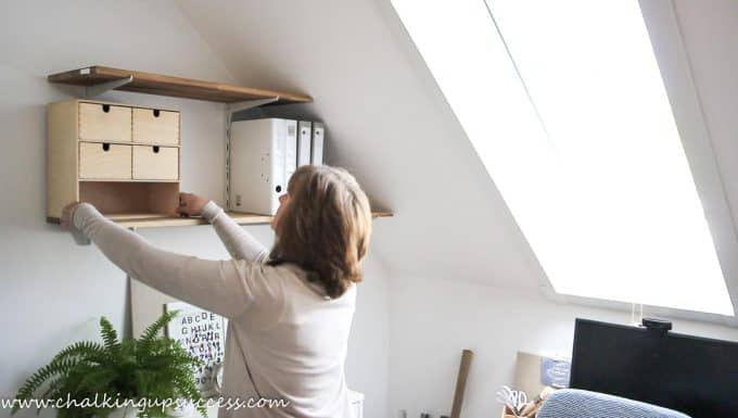 Shows a person adding an IKEA Moppe Storage cupboard to wall shelves A person putting folders up on to shelves - from the post 'How to stle shelves' by Chalking Up Success dot com
