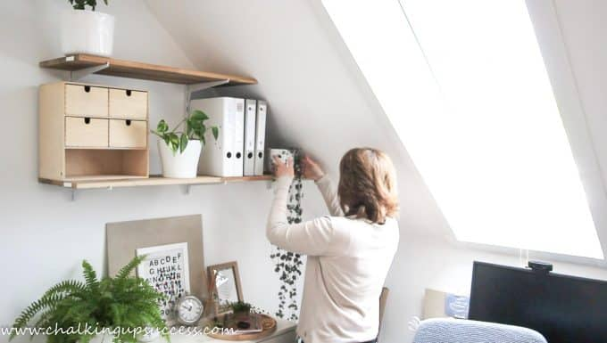 A person adding a trailing heart plant to a set of wall shelves - from the post 'How to stle shelves' by Chalking Up Success dot com