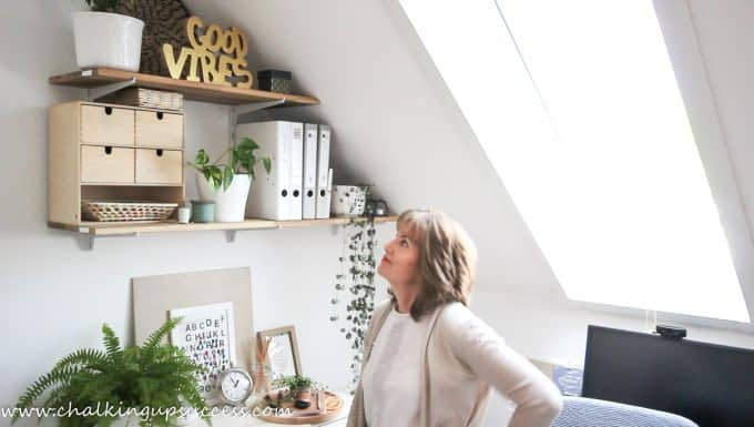 A person looking up and admiring the finished styled shelves - from the post 'How to stle shelves' by Chalking Up Success dot com