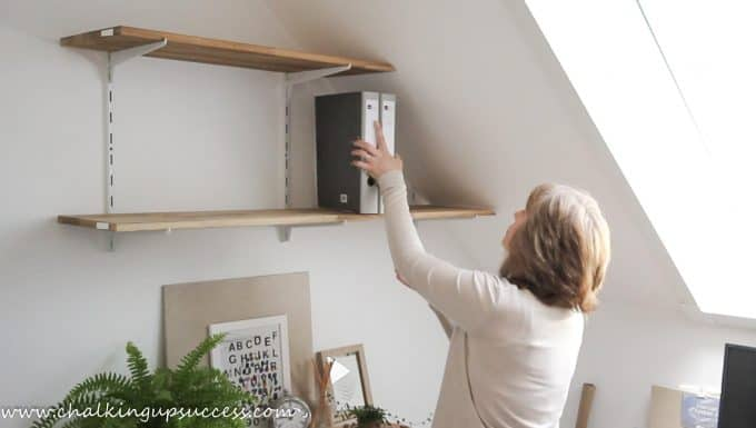 A person putting folders up on to shelves - from the post 'How to stle shelves' by Chalking Up Success dot com