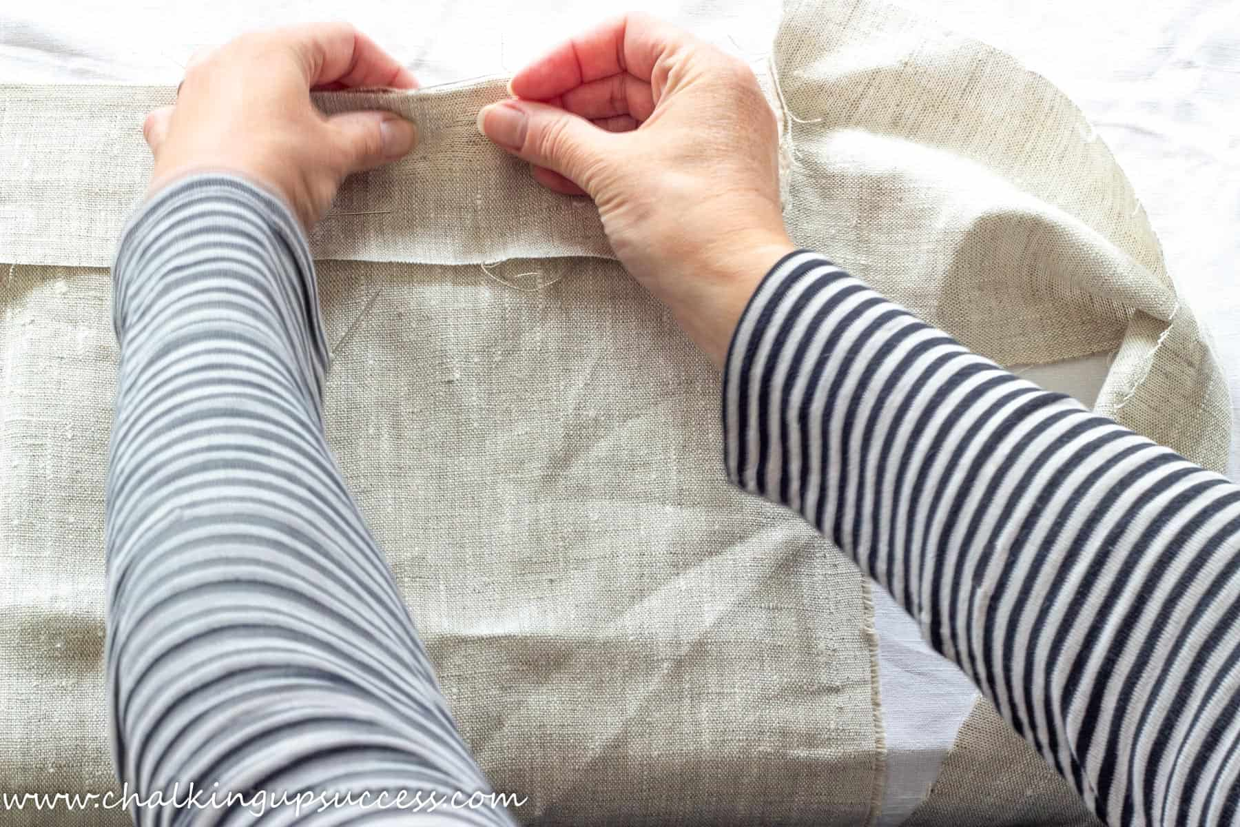 A person pinning together the sides of the linen fabric