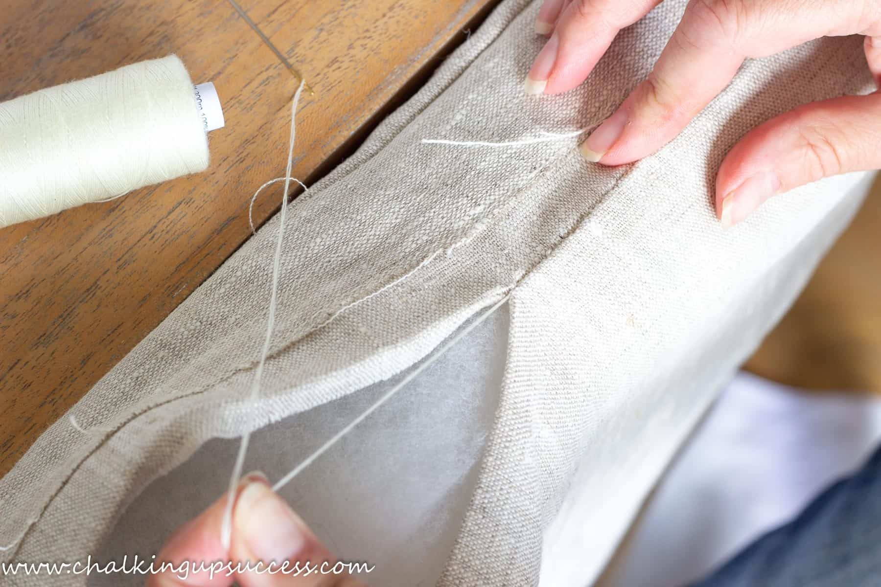 Hand sewing the cushion closed with a 'slip' stitch and pulling the thread tight.