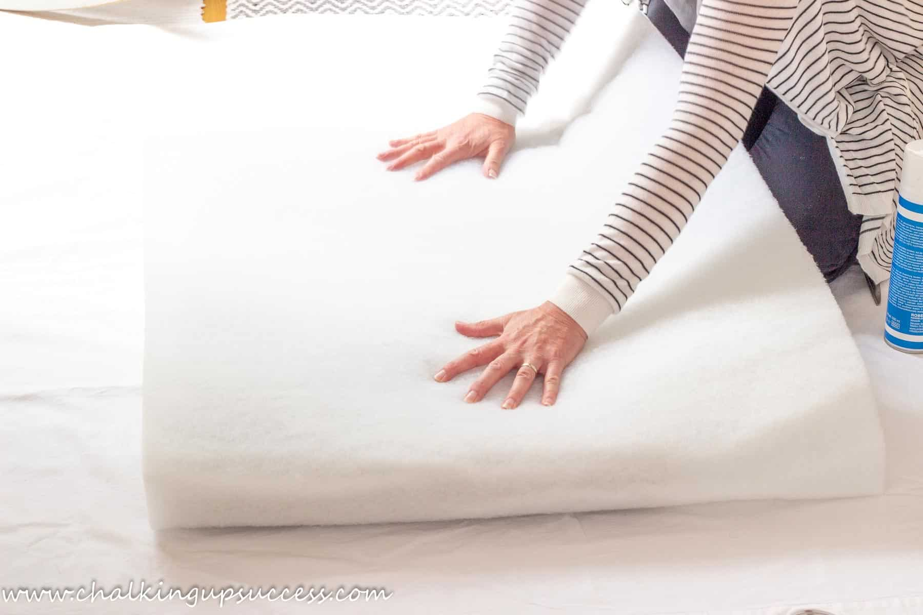 a person wrapping some foam batting around a high density foam cushion pad