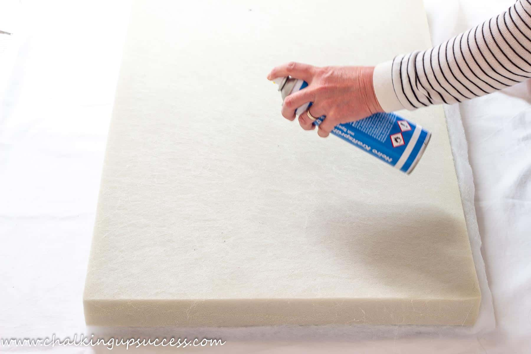 A person spraying a high density foam cushion pad with spray adhesive