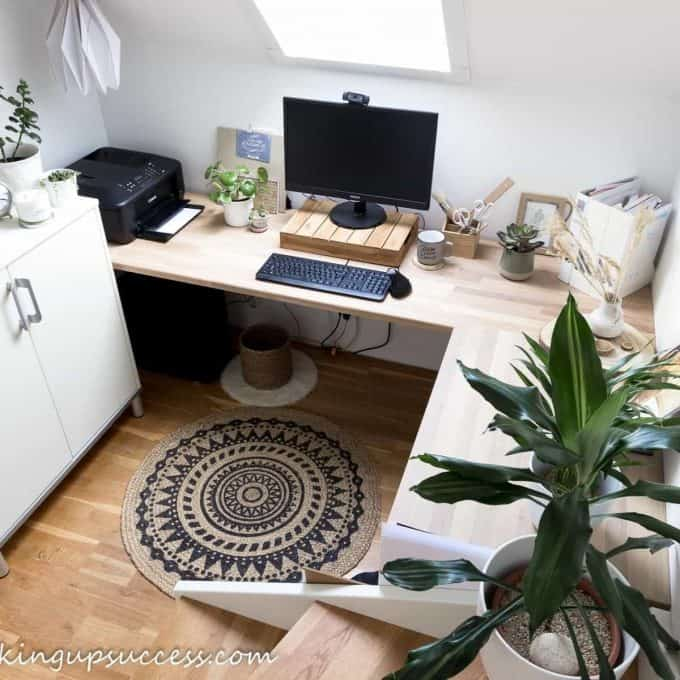 Small, work from home office with an L-shaped corner desk.