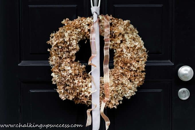 Close up of golden brown dried Hydrangea flowers made into a wreath and hanging on the black door of a blue house.