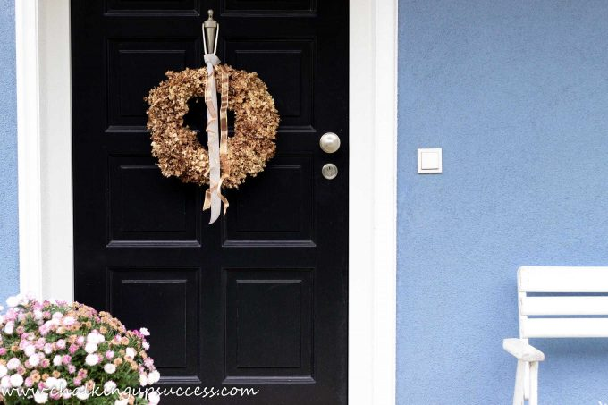 Golden brown dried Hydrangea flowers made into a wreath and hanging on the black door of a blue house.