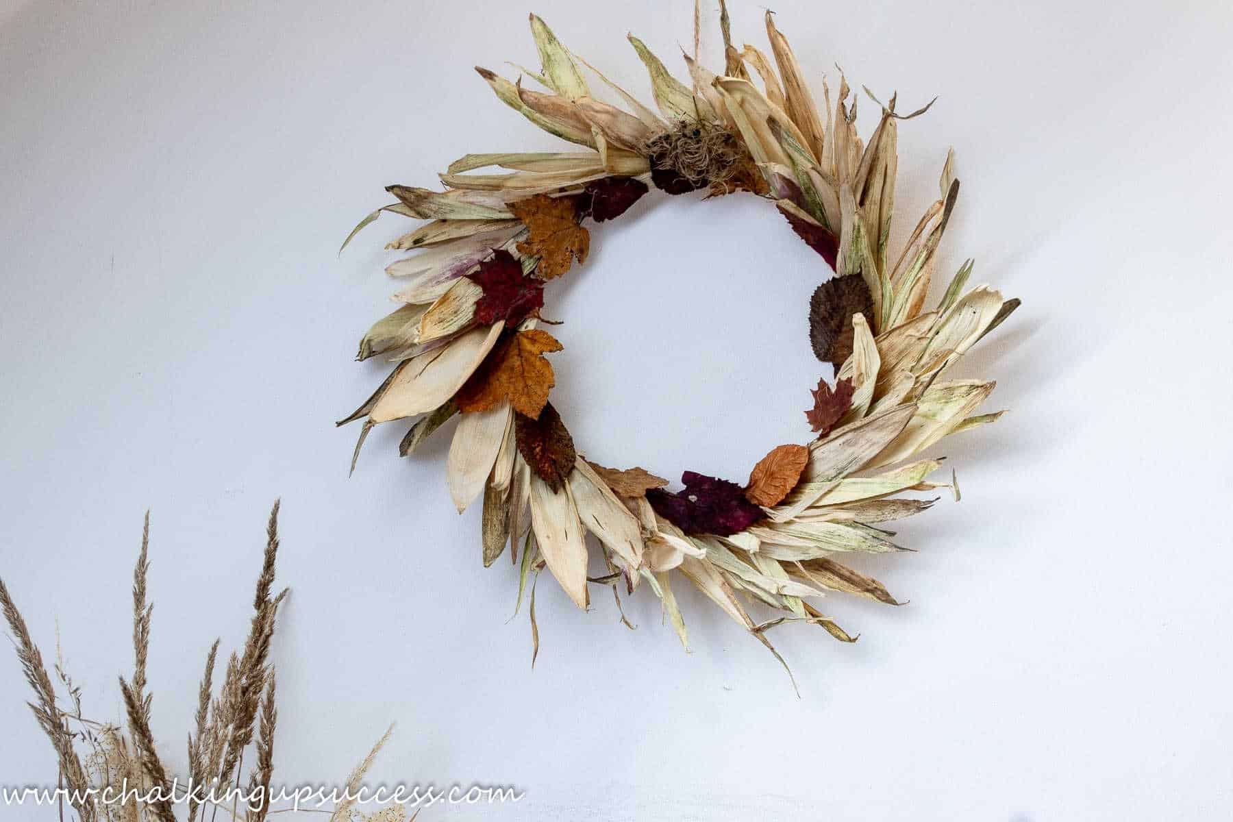 Shows the completed corn husk autumn wreath hanging against a white wall.