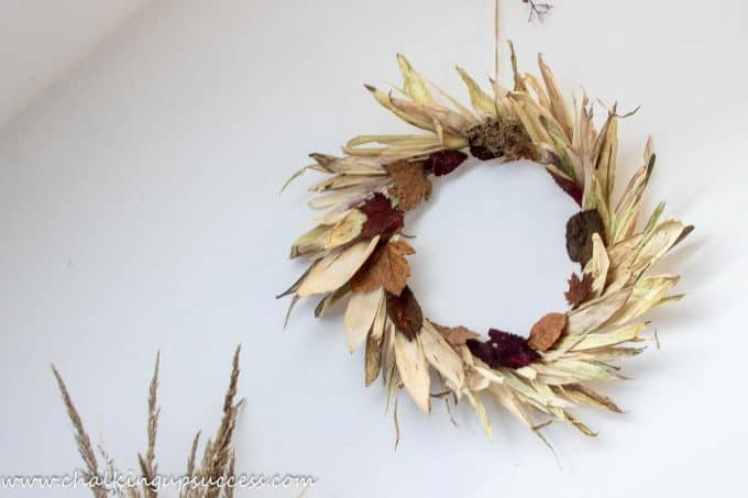 Shows the completed corn husk autumn wreath hanging against a white wall in my home office.