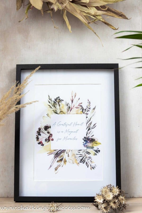 "Free printable wall art. Botanical watercolour print showing autumn flowers in ruset reds, yellows and orange. Text reads ""A grateful heart is a magnet for miracles""."