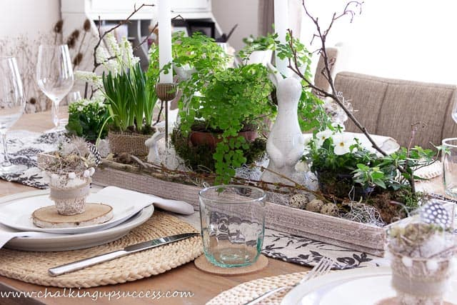 A simple tablescape of spring flowering plants, white Easter bunnies, Easter eggs and spring garden cuttings
