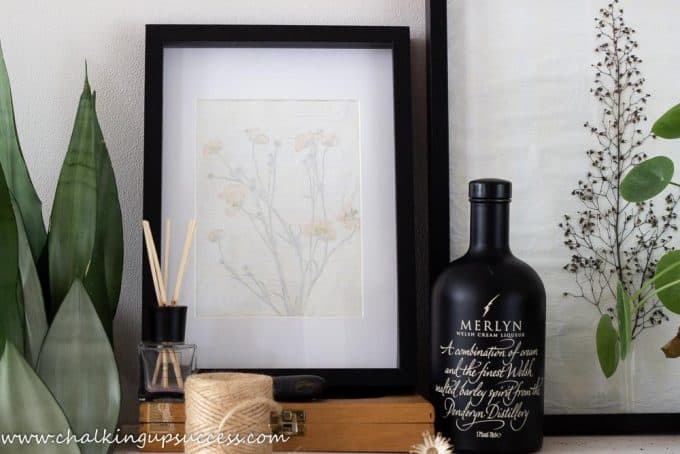Beautiful pressed flower prints with Buttercups and Heuchera standing on a shelf with green plants.