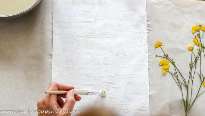 Painting the paper background with paper mache glue ready to make pressed flower prints.