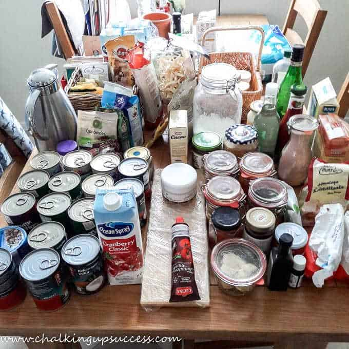 Pantry goods set out on a table ready for organizing - How to organize a small under-stair pantry