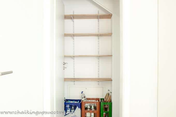Empty shelves ready to be organized in a small under stairs pantry