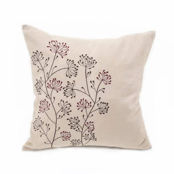 Beige pillow with black and burgundy flowers in seed