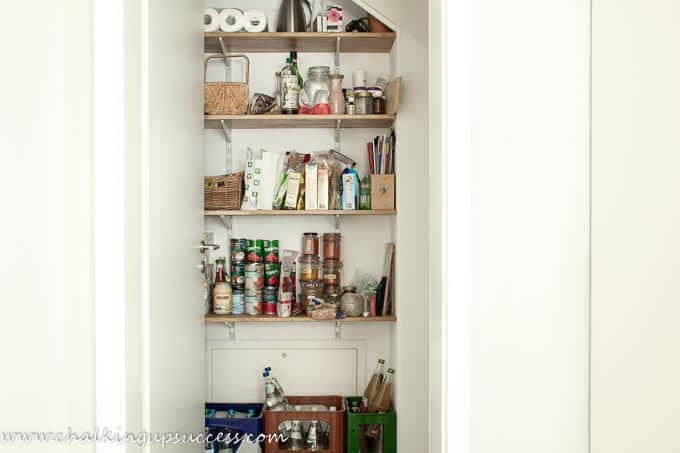 This photo shows how not to organize a small under stair pantry! Pantry items overflowing on the shelves and all the dry goods are mixed up.