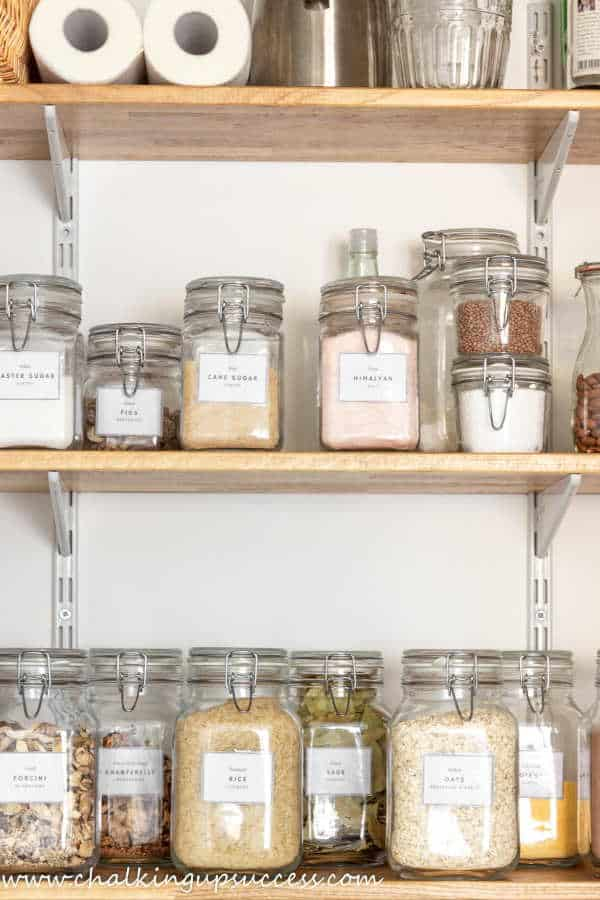 How to organize a small under-stair pantry - photos shows clear glass spring-top jars with labels labelling.