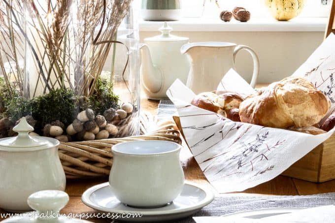 The kitchen table decorated for the autumn home tour and set for breakfast. Denby Linen collection crockery and a bread basket full of breakfast rolls and croissants.